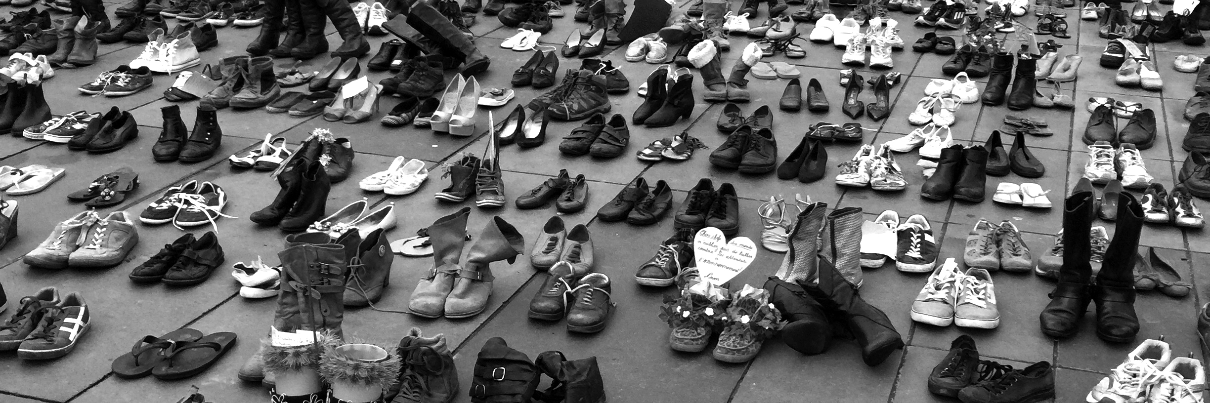 A black and white photo of several pairs of shoes laid out.